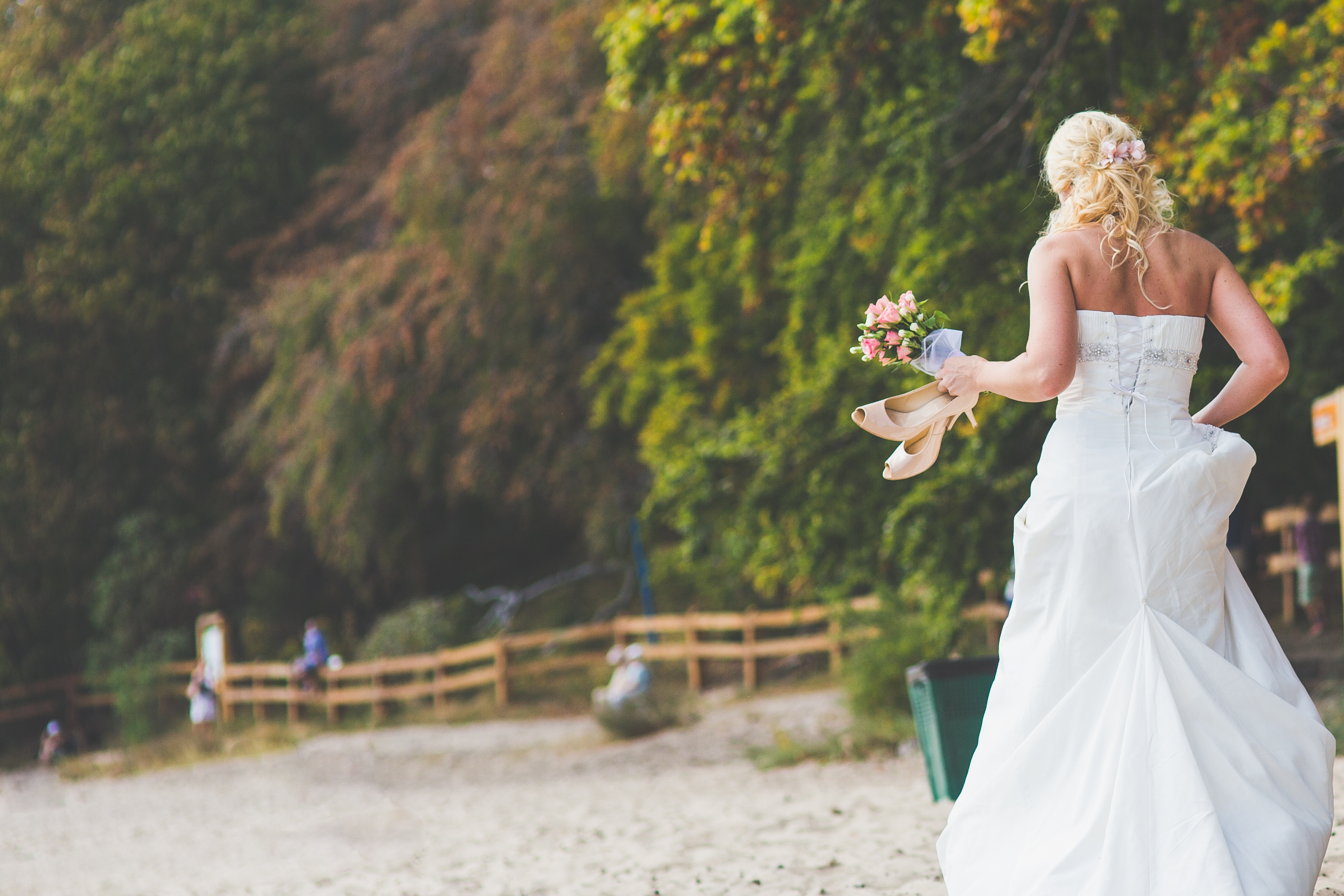 kaboompics.com_Bride walking alone with flowers and shoes